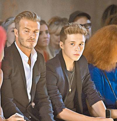 Soccer player David Beckham and his son Brooklyn Beckham watch a model present a creation during the Victoria Beckham Spring/Summer 2015 collection during New York Fashion Week in the Manhattan borough of New York September 7, 2014.    REUTERS/Carlo Allegri (UNITED STATES - Tags: FASHION ENTERTAINMENT)